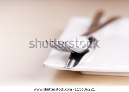 Knife and fork cutlery with a white plate in very shallow focus - stock photo