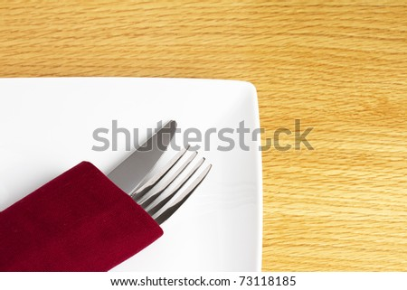 Knife and fork in red napkin on plate