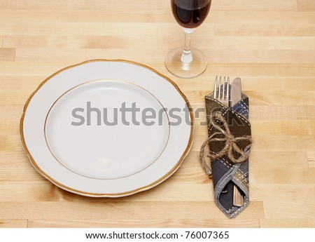knife and fork in textile napkin on wooden table - stock photo