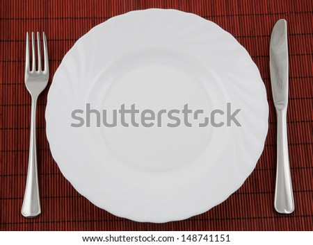 Knife and fork in white plate on red bamboo background - stock photo