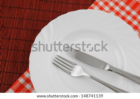 Knife and fork in white plate on red bamboo background with tablecloth - stock photo