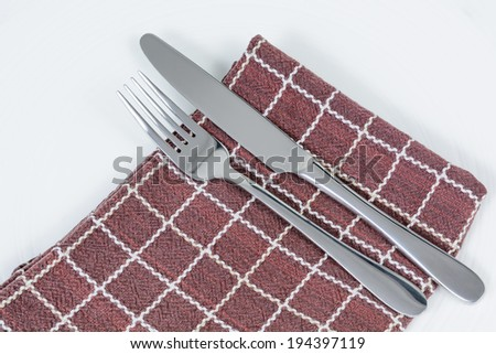 Knife and Fork on a large brown serviette  - stock photo