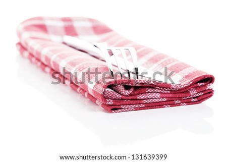 knife and fork on a red checkered towel on white background