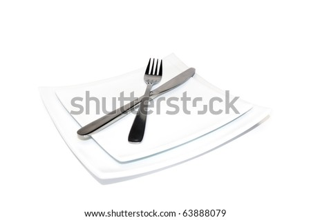 Knife and fork on a white plate isolated