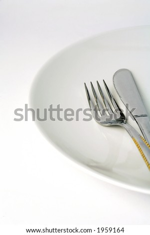 Knife and fork on a white plate, with a splash of gold on the handles.