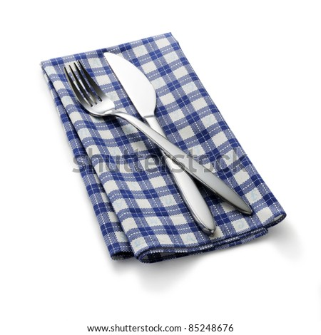 Knife and fork on blue check napkin - stock photo