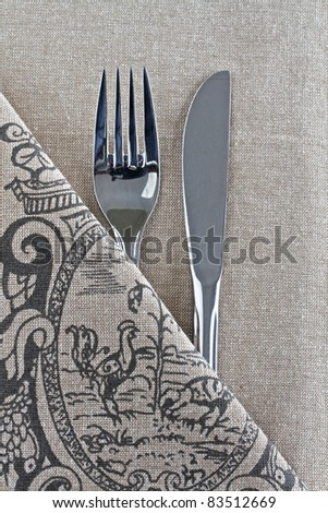 Knife and Fork on linen with design - stock photo