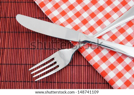 Knife and fork on red bamboo background with tablecloth - stock photo