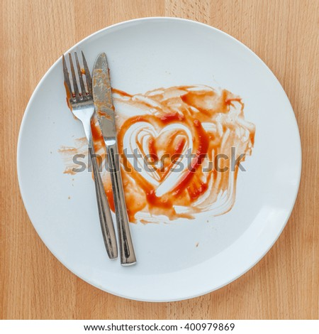 Knife and fork over in finish plate and heart shape ketchup, concept of tasty. - stock photo