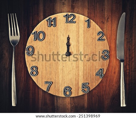 knife and fork with clock plate - stock photo