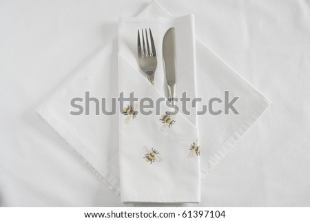 Knife and Fork with embroidered Bee linen napkin and tablecloth - stock photo