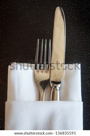 Knife and fork with linen serviette on black background - stock photo
