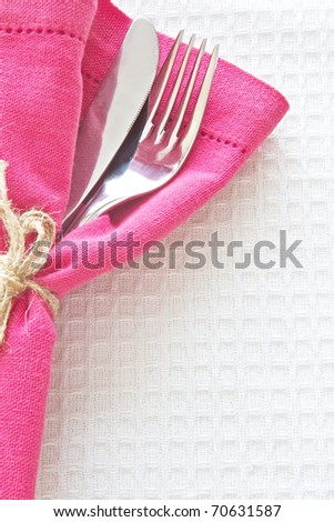 Knife and Fork with pink napkin on white tablecloth - stock photo