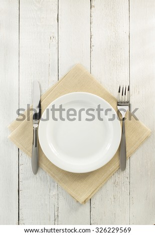 knife and fork with plate at napkin on wooden background - stock photo