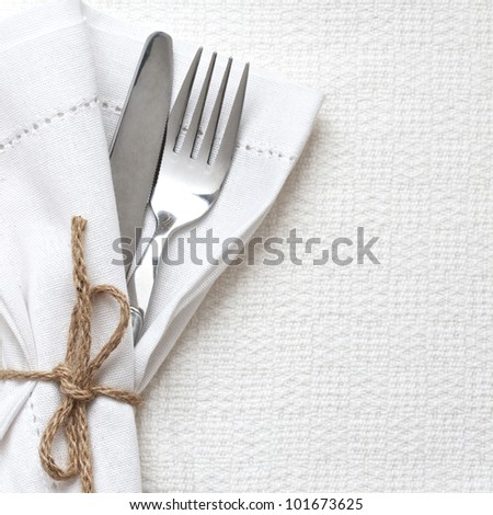 Knife and fork with white linen tied up with string - stock photo