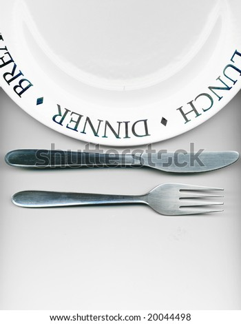 Knife and fork with white plate