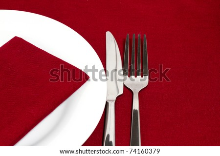 Knife and fork with white plate on red tablecloth - stock photo