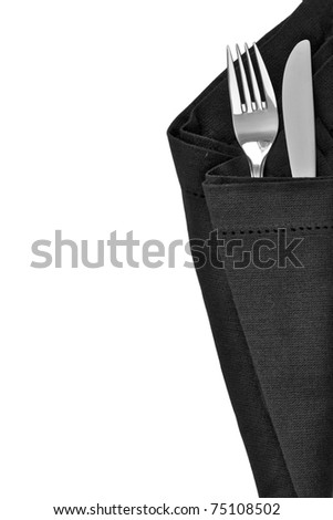 Knife and fork wrapped in a black napkin and isolated on white background with space for text - stock photo