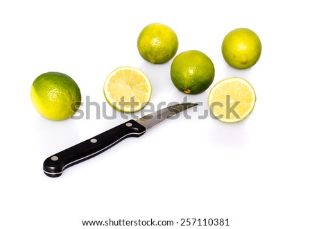 Knife and green fresh limes - whole fruits and two halves - with shadow and reflection on white background - studio shot - stock photo