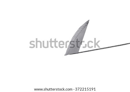Knife blade cutting through surface from underneath resembling a shark fin
