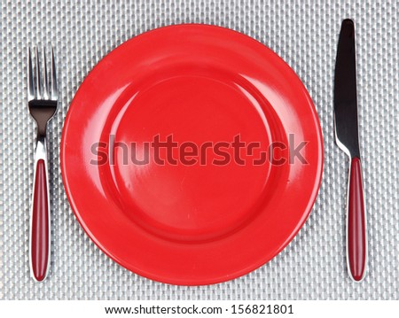Knife, color plate and fork, on color background - stock photo