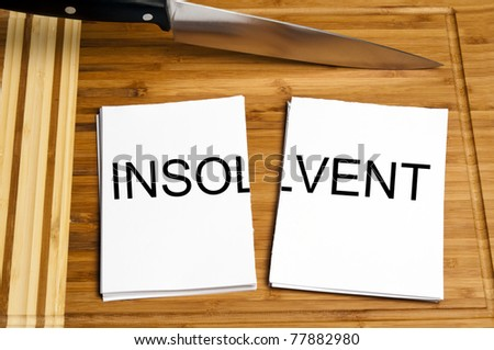 Knife cut paper with insolvent word - stock photo