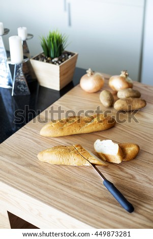 Knife cutting baguette on the wooden board