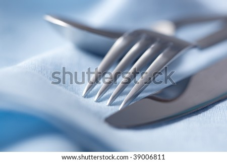 Knife, fork and spoon on blue linen napkin.  Very shallow depth of field. - stock photo
