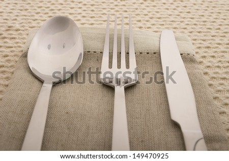 Knife, fork and spoon with linen serviette - stock photo