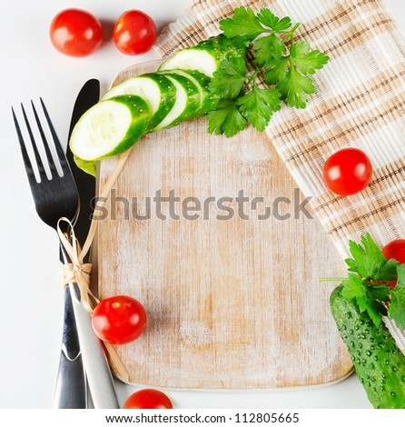 Knife , fork and wood cutting board with fresh vegetables - stock photo
