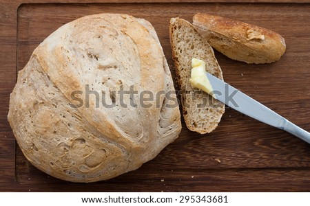 knife, home made bread and butter on wooden board - studio shot - stock photo