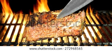 Knife In The Pork Ribs On The Hot Flaming BBQ Grill, Flames of Fire On The Black Background - stock photo