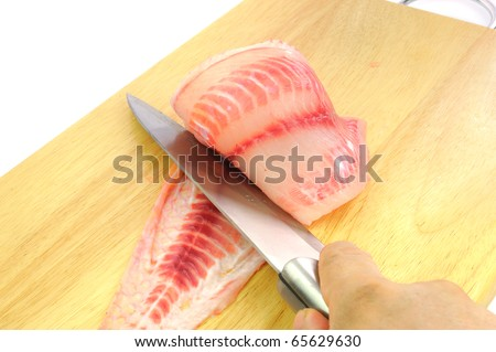 Knife on a hand slicing Red tilapia preparation for steak on wooden Cutting Board. - stock photo