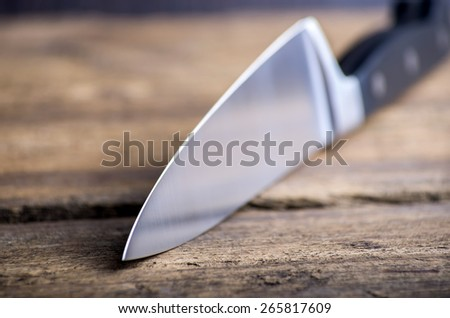 Knife on rustic kitchen table with copy space - stock photo