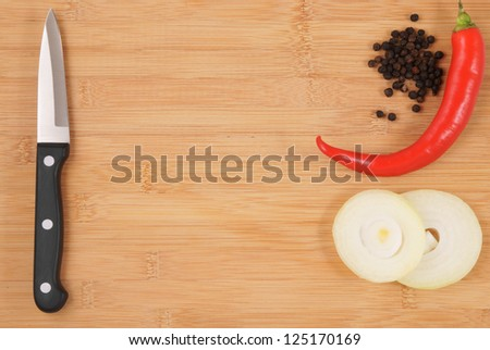 Knife, onion and pepper on cutting board - stock photo