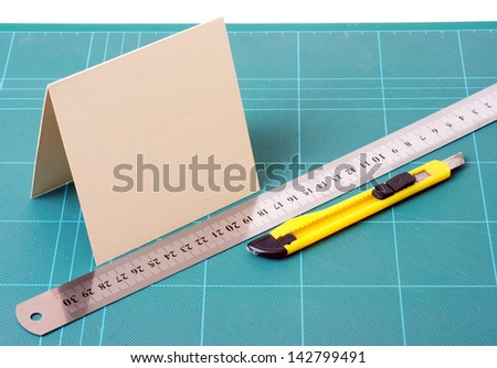 knife, paper, and ruler on the cutting board