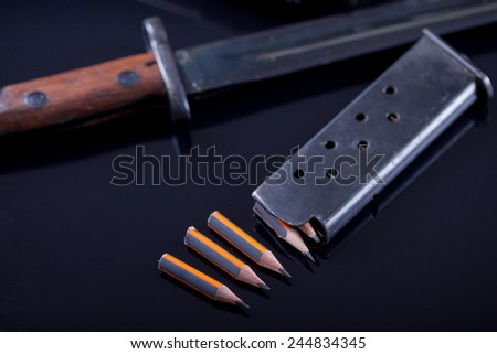 knife, pen in the form of bullet on black background - stock photo