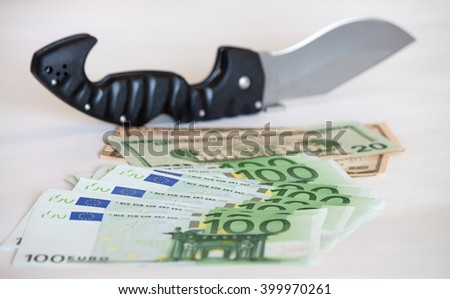 Knife placed on pile of american dollar and euro bills om white background - stock photo
