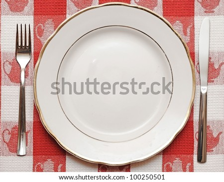 Knife, plate and fork on red tablecloth - stock photo