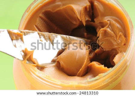 Knife scooping out peanut butter - stock photo