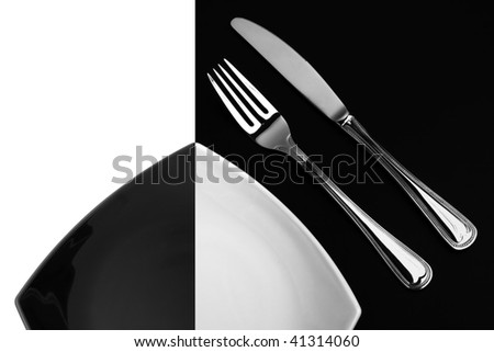 Knife, square white plate and fork on black background - stock photo