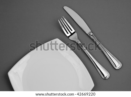 Knife, square white plate and fork on gray background