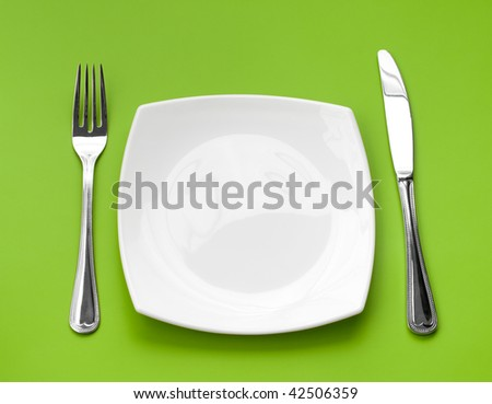 Knife, square white plate and fork on green background - stock photo