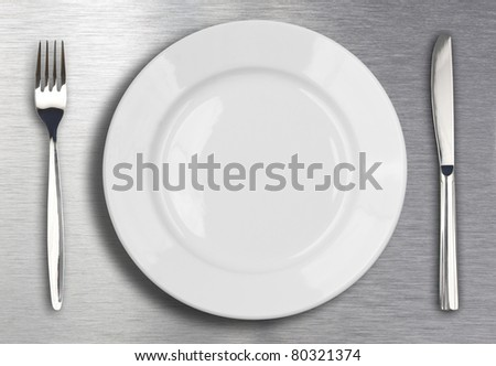 Knife, white plate and fork on metal background - stock photo