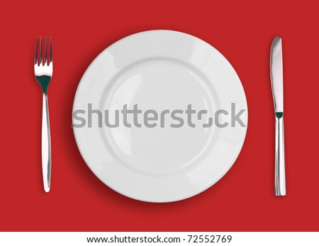 Knife, white plate and fork on red background - stock photo