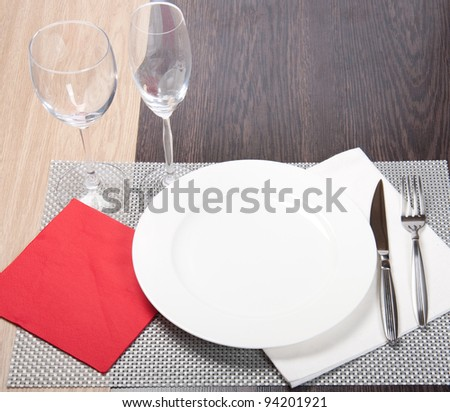 Knife, white plate and fork on silver background