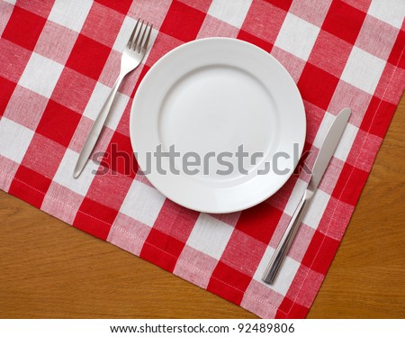 Knife, white plate and fork on wooden table with red checked tablecloth - stock photo