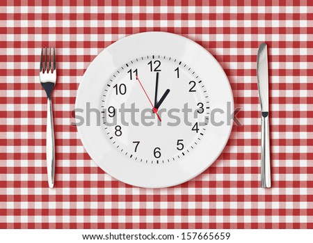 Knife, white plate with clock face and fork on red picnic table cloth - stock photo