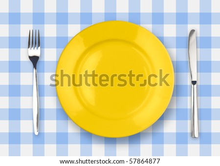 Knife, yellow plate and fork on yellow checked tablecloth - stock photo