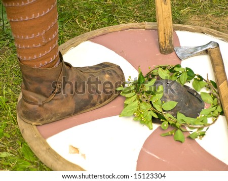 Knight leg standing at round shield near axe - stock photo